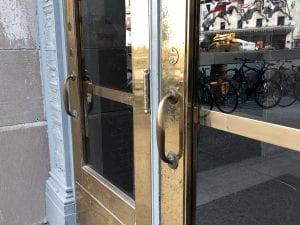 Worn brass pull handles on brass clad doors
