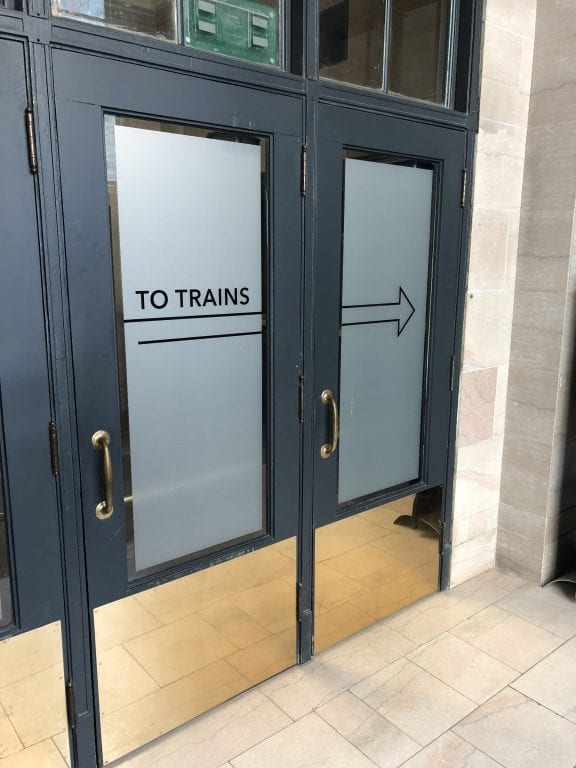 """Doors marked """"To Trains"""" with brass pulls and kickplates"""