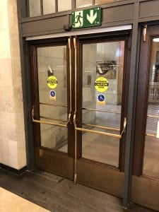 Pair of automatic doors with brass vertical rod exit devices