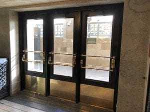 Bank of doors with brass push rails and exit devices
