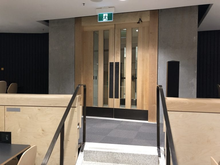 Pair of wood doors with lites and bronze hardware