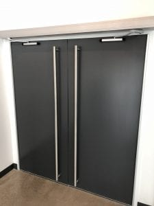 Black doors with operator, pulls and continuous hinges