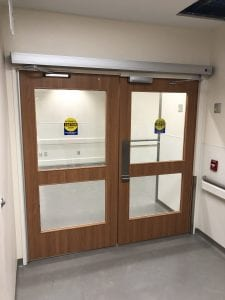 Wood double egress doors in hospital corridor