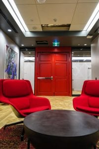 Red chairs with red door and exit device in background