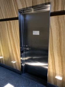 stainless door in wood-clad wall