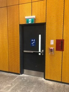 exit door on orange perforated wall