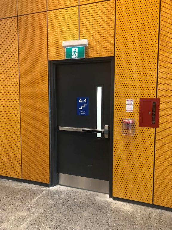 exit door on orange perforated wall